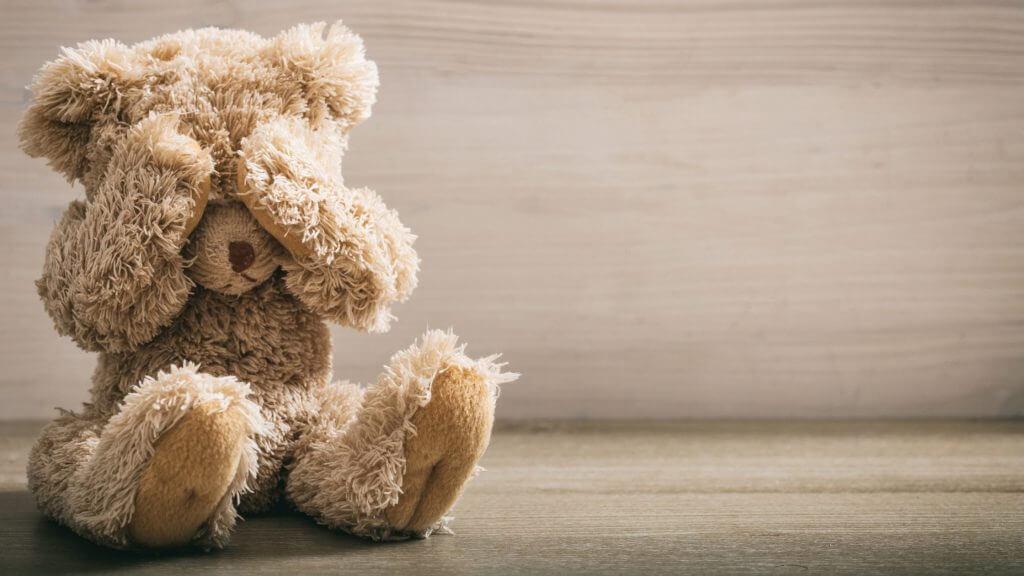目を覆うクマのぬいぐるみの写真